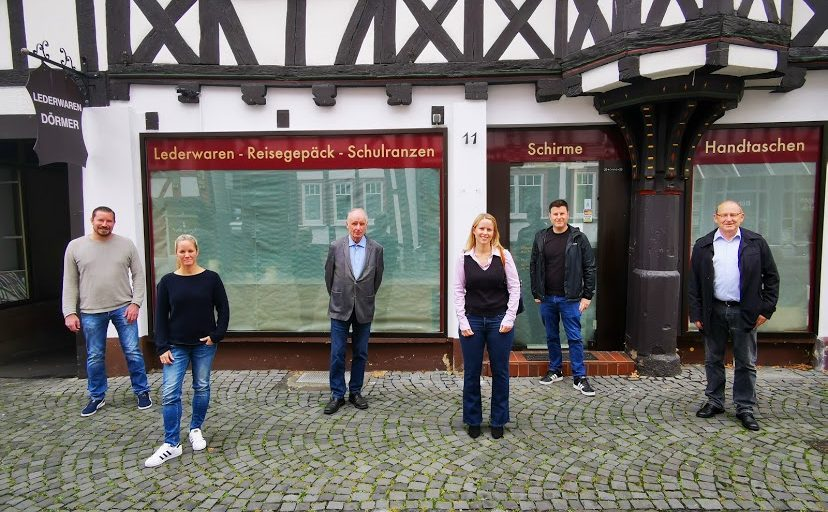 """Foto von Florian Uhl, Susanne Pucher, Helmut Jachimsky, Jana Nathalie Burg, Dennis Pucher, Prof. Dr. Klaus Doll vor dem Licher Unternehmen """"Lederwaren Dörmer"""""""